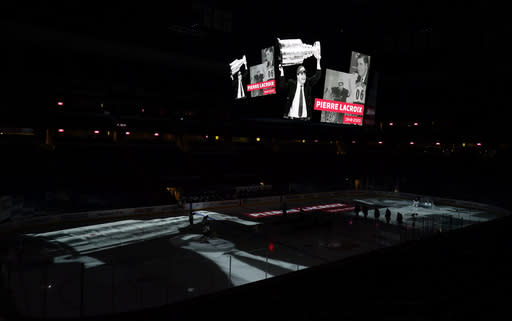 A video tribute is played overhead scoreboard to former Colorado Avalanche general manager and president Pierre Lacroix, before the Avalanche's NHL hockey game against the St. Louis Blues on Wednesday, Jan. 13, 2021, in Denver. Lacroix died last month from complications of COVID-19. (AP Photo/David Zalubowski)