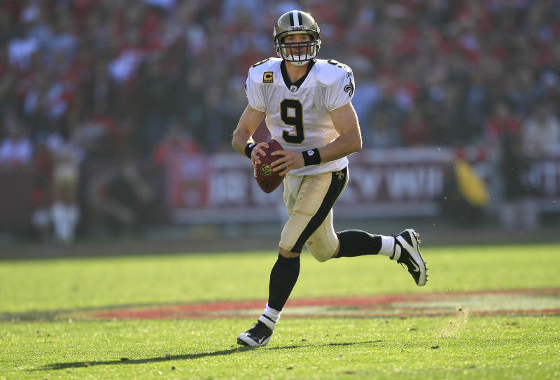 FILE - In this Jan. 14, 2012, file photo, New Orleans Saints quarterback Drew Brees rolls out to pass against the San Francisco 49ers during the second quarter of an NFL divisional playoff football game in San Francisco. Brees has agreed to a five-year, $100 million contract with the Saints, with $60 million guaranteed, on Friday, July 13, 2012, a person familiar with the deal tells The Associated Press. (AP Photo/Marcio Jose Sanchez, File)