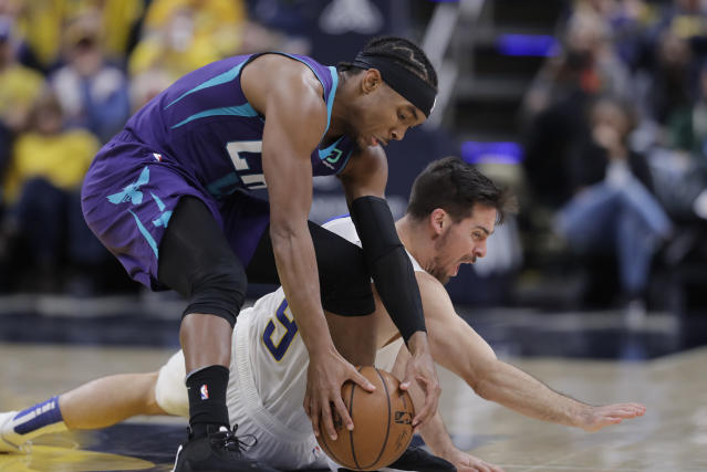 Charlotte Hornets' Devonte' Graham (4) recovers the ball against Indiana Pacers' T.J. McConnell (9) during the second half of an NBA basketball game, Sunday, Dec. 15, 2019, in Indianapolis. (AP Photo/Darron Cummings)