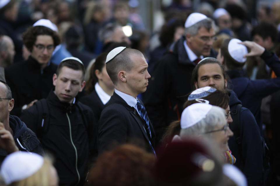 FILE - In this Wednesday, April 25, 2018 file photo, people wear Jewish skullcaps, as they attend a demonstration against an anti-Semitic attack in Berlin. As Jews around the world gather Sunday night to mark the beginning of Yom Kippur, many in Germany remain uneasy about going together to their houses of worship to pray, a year after a white-supremacist targeted a synagogue in the eastern city of Halle on the holiest day in Judaism. (AP Photo/Markus Schreiber, file)
