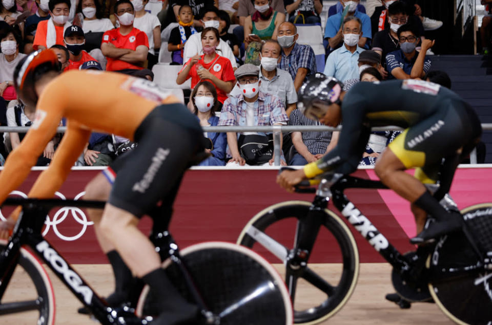 Spectators wearing face masks watch Netherlands' Harrie Lavreysen and Malaysia's Muhammad Shah Firdaus Sahrom as they compete in a heat of the men's track cycling sprint 1/32 finals during the Tokyo 2020 Olympic Games at Izu Velodrome in Izu, Japan, August 4, 2021. — AFP pic