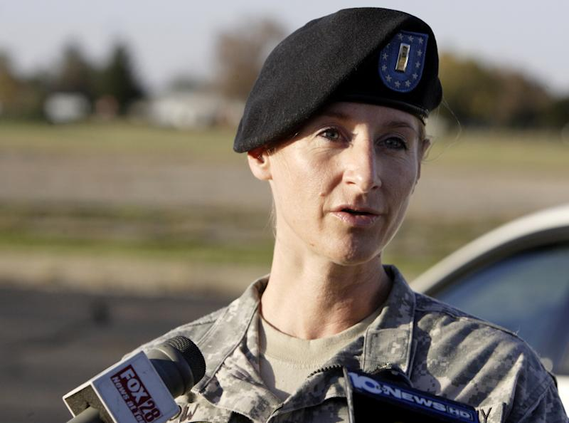 First Lieutenant Kimberly Snow of the National Guard public affairs office answers questions at Rickenbacker International Airport in Columbus, Ohio, about four soldiers who were injured at the airport after they parachuted from a plane during an airborne training operation, Wednesday, Oct. 20, 2010. (AP Photo/Paul Vernon)