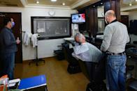 Jordanians follow the latest political developments in their country on a television set inside an Amman barber shop