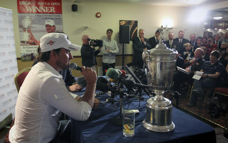 FILE - In this Wednesday, June, 23, 2010, file photo, U.S. Open golf champion Graeme McDowell receives a warm welcome from members of Rathmore Golf Club, in Portrush, Northern Ireland. McDowell was among three major champions from Northern Ireland that sparked interest in the British Open returning to Royal Portrush for the first time since 1951. (AP Photo/Peter Morrison, File)