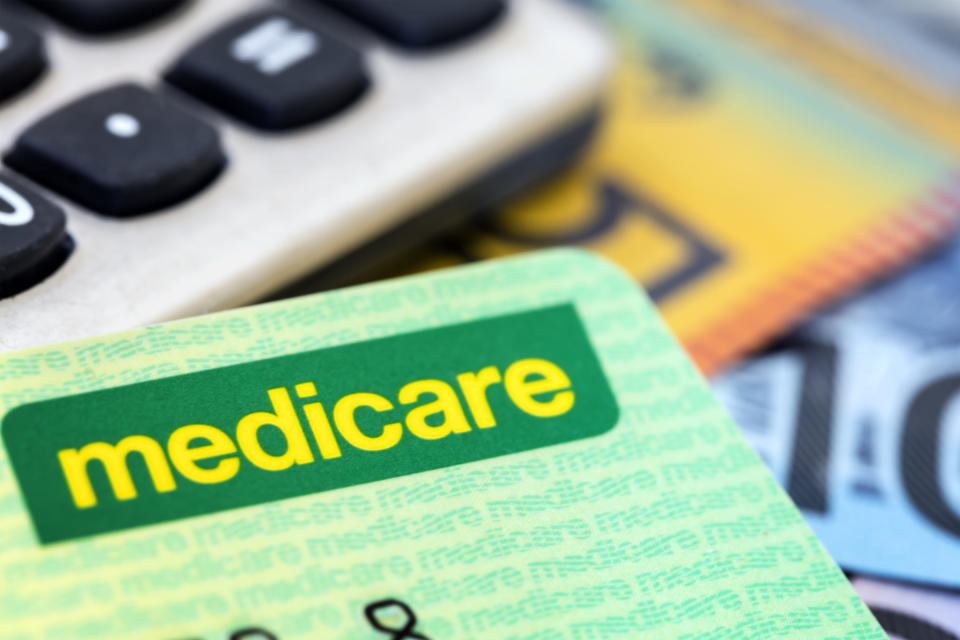 Australian Medicare card with calculator and cash background.