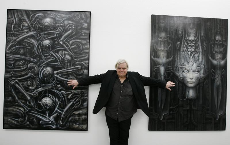 "FILE - In this June 29, 2007 file picture Swiss artist H.R. Giger poses with two of his works at the art museum in Chur, Switzerland. H.R. Giger, who designed the creature in Ridley Scott's sci-fi horror classic ""Alien,"" has died at age 74 from injuries suffered in a fall. Sandra Mivelaz, administrator of the H.R. Giger museum in Chateau St. Germain told The Associated Press Tuesday May 13, 2014 that Giger had died in a hospital the day before. Giger received a 1979 Academy Award for special effects in 'Alen'. Giger's works, often showing macabre scenes of humans and machines fused into hellish hybrids, influenced a generation of movie directors and inspired an enduring fashion for ""biomechanical"" tattoos. (AP Photo/Keystone,Arno Balzarini,File)"
