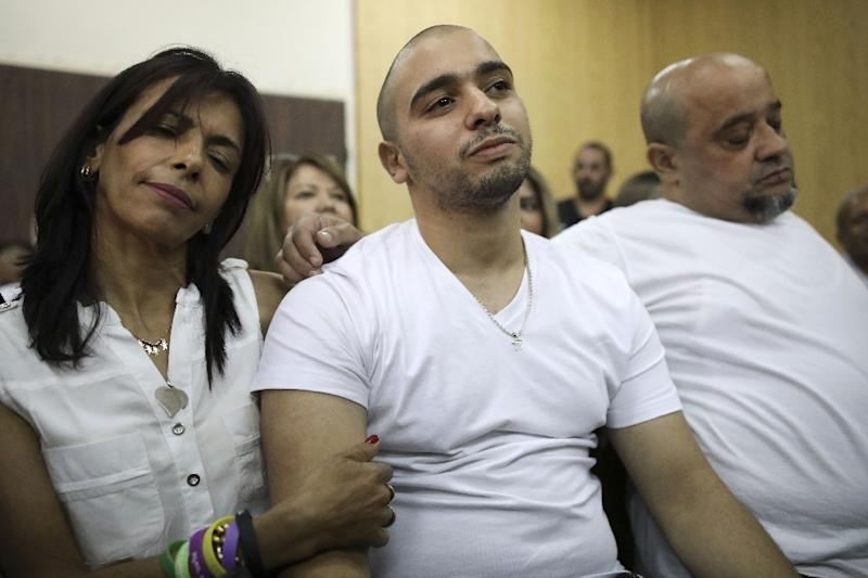 Israeli soldier Elor Azaria (C), who shot dead a wounded Palestinian assailant in March 2016 sits between his parents during a hearing at a military court in Tel Aviv on July 30, 2017