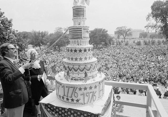 <p>James Rhoads of the National Archives prepares to cut a Bicentennial birthday cake in Washington, D.C., Sunday, July 4, 1976 as thousands look on. Standing next to Rhoads is actor Glenn Taylor, dressed in colonial costumes, who read the Declaration of Independence during the ceremony. (Photo: AP) </p>