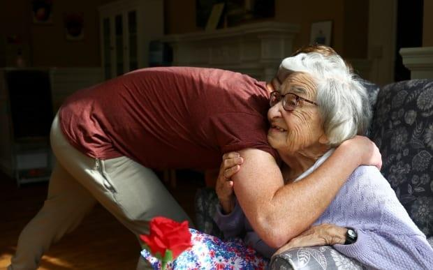 Community coordinator Terence Surin hugs Joan Brock, 101, who is a resident at Alexander House Care Home in Wimbledon, as COVID-19 restrictions continue to ease in London on May 17, 2021.