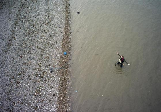 busker plays his electric guitar while standing in the River Thames at low tide along the south bank in London March 13, 2012.