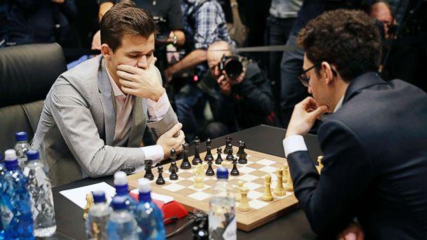 PHOTO: Reigning chess world champion Magnus Carlsen, left, from Norway, plays Italian-American challenger Fabiano Caruana in the first few minutes of round 12 of their World Chess Championship Match in London, Nov. 26, 2018. (Matt Dunham/AP)