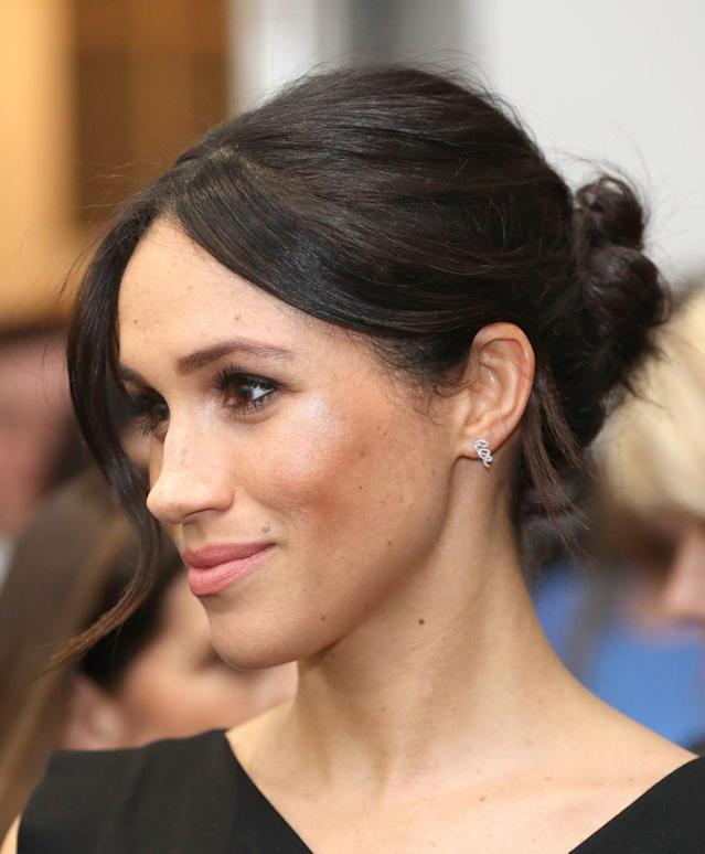 <p>For her second evening event, Meghan stuck to her instincts and worked her go-to bun. Though the back may be fashionably messy, the front is slick, and her wisps of hair are perfectly curled. (Photo: Getty Images) </p>