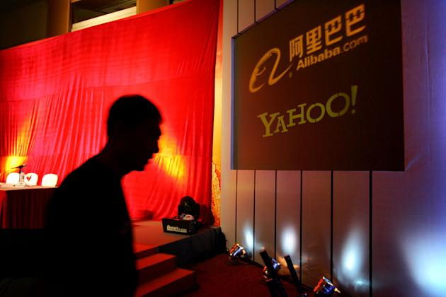 In this file photo, a man walks past a sign showing the Yahoo! and Alibaba.com logos. (AP)