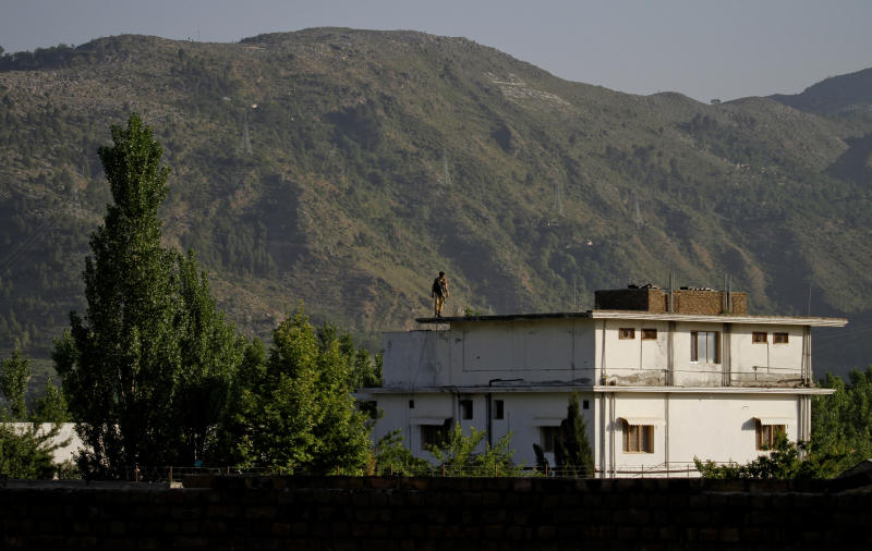 A Pakistan army soldier stands on top of the house where it is believed al-Qaida leader Osama bin Laden lived in Abbottabad, Pakistan on Monday, May 2, 2011. Bin Laden, the mastermind behind the Sept. 11, 2001, terror attacks that killed thousands of people, was slain in his hideout in Pakistan early Monday in a firefight with U.S. forces, ending a manhunt that spanned a frustrating decade. (AP Photo/Anjum Naveed)