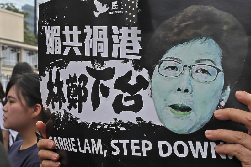 "In this Monday, June 17, 2019, photo, a protester holds a placard baring an image of Hong Kong Chief Executive Carrie Lam as they gather near the Legislative Council to continue protest against the unpopular extradition bill in Hong Kong. The various pro-democracy groups that helped drive and organize the protests are pushing for Lam's resignation and the permanent scrapping of what they call the ""evil"" extradition bill. (AP Photo/Kin Cheung)"