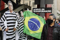 A man looks at a cardboard cutout of Brazilian President Jair Bolsonaro in prisoner garb during a demonstration against Bolsonaro's handling of the coronavirus pandemic and economic policies protesters say harm the interests of the poor and working class on Paulista Avenue, in Sao Paulo, Brazil, Saturday, June 19, 2021. Brazil's COVID-19 death toll is expected to surpass the milestone of 500,000 deaths on Saturday night. (AP Photo/Marcelo Chello)