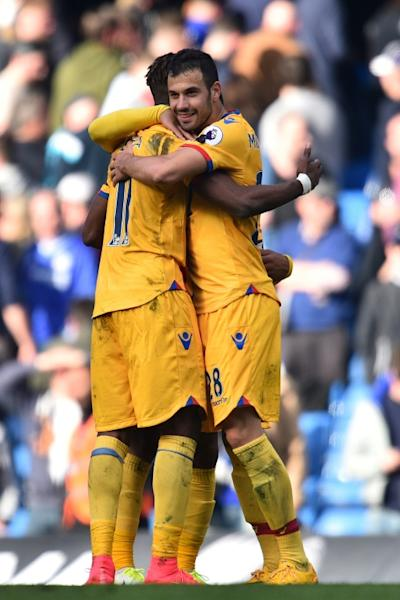 Crystal Palace's Luka Milivojevic (R) and Crystal Palace's Wilfried Zaha embrace on the pitch at the final whistle at Stamford Bridge in London on April 1, 2017