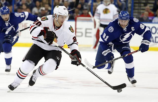 Chicago Blackhawks left wing Brandon Saad (20) controls the puck ahead of Tampa Bay Lightning center Steven Stamkos (91) during the first period of an NHL hockey game Friday, Feb. 27, 2015, in Tampa, Fla. (AP Photo/Brian Blanco)