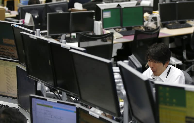An employee of a foreign exchange trading company looks at monitors in Tokyo