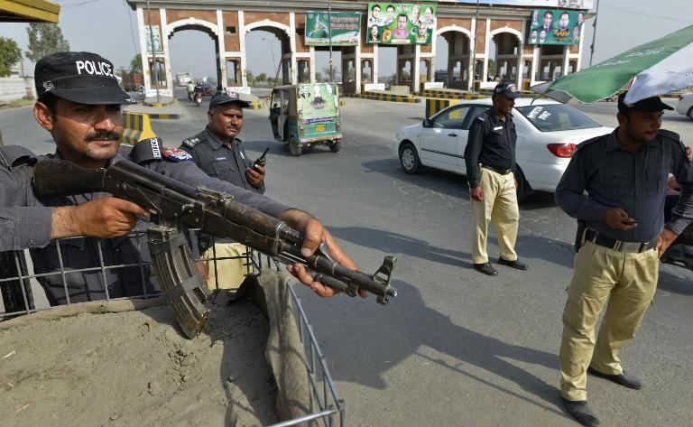Pakistani policemen keep watch at a checkpoint in Lahore, on June 16, 2014