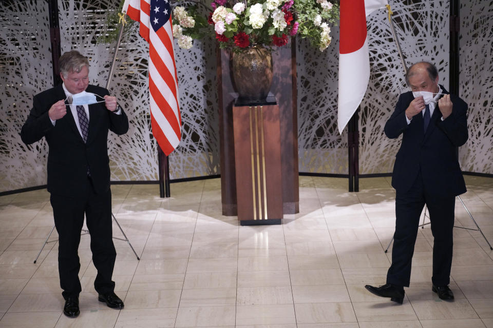 U.S. Special Representative for North Korea Stephen Biegun, left, and Japanese Vice Foreign Minister Takeo Akiba, right, take off their protective masks for a photo session prior to their bilateral meeting at Iikura Guest House Thursday, July 9, 2020, in Tokyo. (AP Photo/Eugene Hoshiko, Pool)