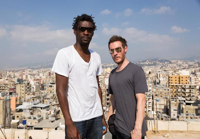 """Graffiti artist Banksy has often been speculated to be Robert """"3D"""" del Naja (R), seen here visiting a Palestinian refugee camp south of Beirut in 2014 with Massive Attack co-star Grantley """"Daddy G"""" Marshall (AFP Photo/Maya HAUTEFEUILLE)"""