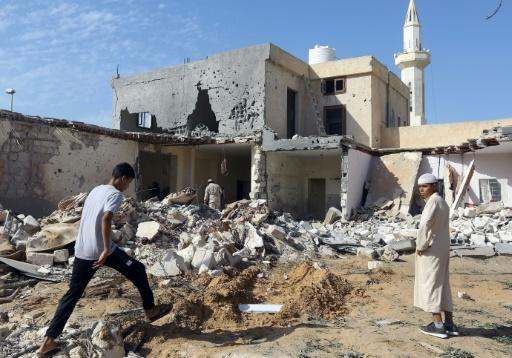 Libyans check the site of an air strike on the southern outskirts of Tripoli last year