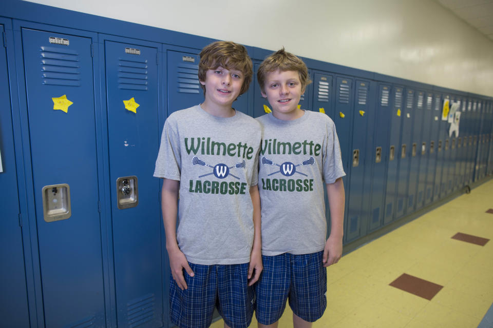 In this Thursday, June 6, 2013 photo, Henry Pigott, left, and his twin brother, Evan, one of the 24 sets of twins from Highcrest Middle School in Wilmette, Ill., pose for a portrait at the school. The group is attempting to break a Guinness World record for the amount of twins in one grade which is currently 16 sets. (AP Photo/Scott Eisen)