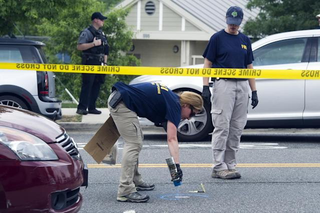 <p>FBI Evidence Response Team members mark evidence at the scene of a multiple shooting in Alexandria, Va., Wednesday, June 14, 2017, where House Majority Whip Steve Scalise of La., and others, were shot at a congressional baseball practice. (Photo: Cliff Owen/AP) </p>