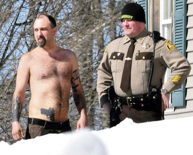 "In this Tuesday, March 18, 2014 photo, Michael Smith, left, stands beside a Somerset County Sheriff deputy outside his home in Norridgewock, Maine. Officers armed with assault rifles descended on Smith's home after members of a tree removal crew he'd told to clear off his property reported that he had a gun. The ""gun"" the tree crew had seen on Smith actually was a life-sized tattoo of a handgun on his stomach. (AP Photo/Morning Sentinel, David Leaming)"