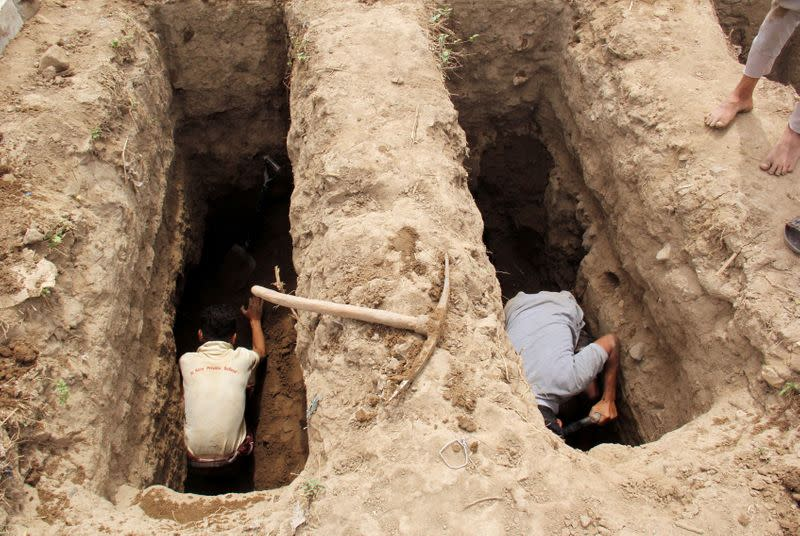 FILE PHOTO: People dig graves at a cemetery where victims of the coronavirus disease (COVID-19) are buried in Taiz