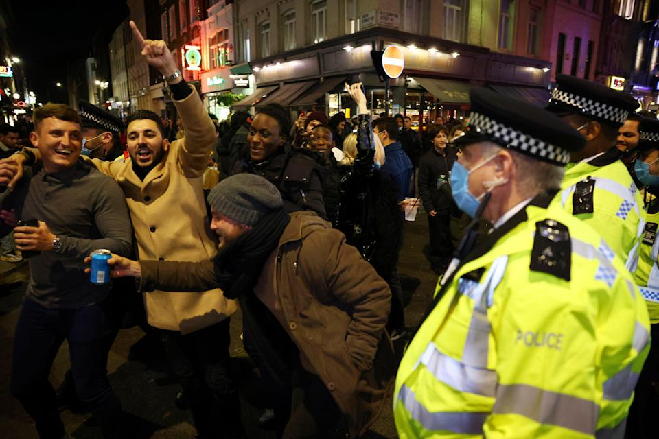 People in the street while police officers look on as pubs close ahead of the second national lockdown, in Soho, London (REUTERS)