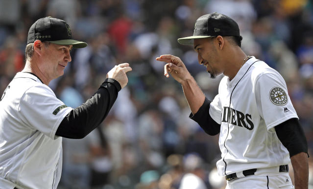 Seattle Mariners manager Scott Servais, left, gestures with closing pitcher Edwin Diaz after the team defeated the Texas Rangers in a baseball game Monday, May 28, 2018, in Seattle. (AP Photo/Elaine Thompson)