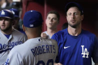 Los Angeles Dodgers' Max Scherzer talks to manager Dave Roberts (30) in the dugout before the team's baseball game against the Arizona Diamondbacks, Saturday, July 31, 2021, in Phoenix. (AP Photo/Rick Scuteri)