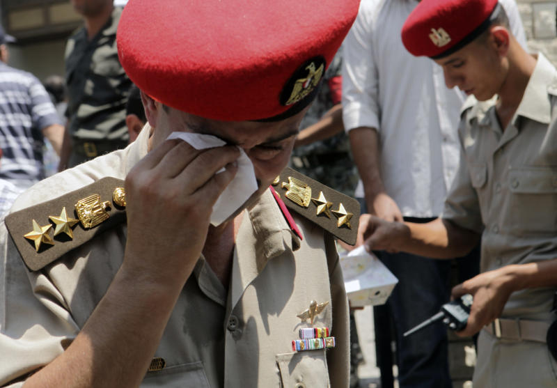 An Army honor officer wipes his eye at the funeral of one of 16 soldiers killed in an attack over the weekend by suspected militants in Sinai in Cairo, Egypt Tuesday Aug. 7, 2012. Mourners prayed for the dead at a mosque in an east Cairo suburb before the coffins, wrapped in Egypt's red-white-and-black flag, were taken to a nearby square where a military funerary ceremony led by Defense Minister Hussein Tantawi was held. (AP Photo/Thomas Hartwell)