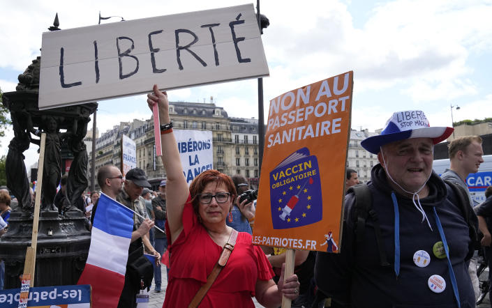 """A protestor holds a sign which reads in French, """"freedom"""" and """"no to the Covid passport"""" as she attends a demonstration in Paris, France, Saturday, July 31, 2021. Demonstrators gathered in several cities in France on Saturday to protest against the COVID-19 pass, which grants vaccinated individuals greater ease of access to venues. (AP Photo/Michel Euler)"""