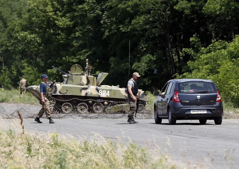 Ukrainian servicemen stop a car at a checkpoint outside the eastern Ukrainian town of Slaviansk