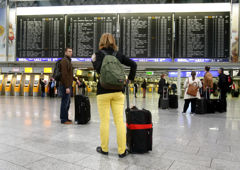 Passengers stand in a terminal at the Frankfurt airport as Lufthansa pilots went on a three-day strike in Frankfurt, Germany, Wednesday, April 2, 2014. Germany's Lufthansa said it has canceled almost 900 domestic and intercontinental flights on the first day of a three-day strike by the pilots' union. Airline spokeswoman Barbara Schaedler said that up to 900 flights were canceled for Wednesday and that it expects to cancel about 3,800 flights altogether, affecting more than 425,000 passengers. (AP Photo/Michael Probst)