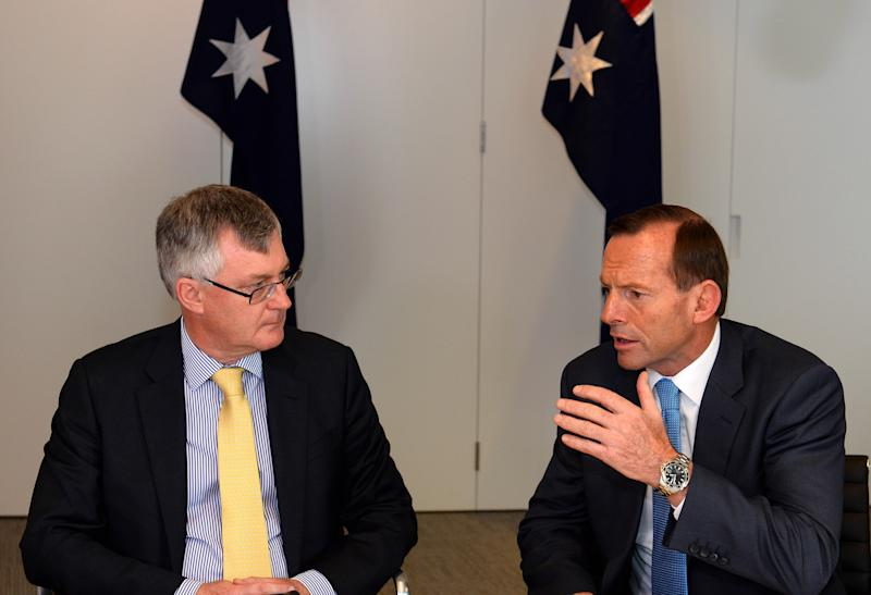 Australian Prime Minister-elect Tony Abbott, right, meets with Treasury Secretary Martin Parkinson in Sydney Sunday, Sept. 8, 2013. A new government prepared to take control of Australia on Sunday, with policies to cut pledges in foreign aid and to wind back greenhouse gas reduction measures in an effort to balance the nation's books. (AP Photo/Saeed KHAN, Pool)
