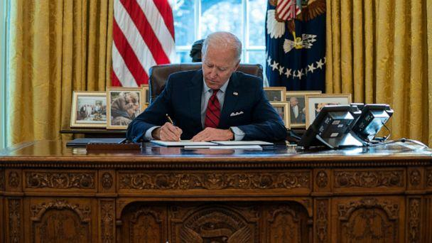 PHOTO: President Joe Biden signs a series of executive orders on health care, in the Oval Office of the White House in Washington, Jan. 28, 2021. (Evan Vucci/AP)