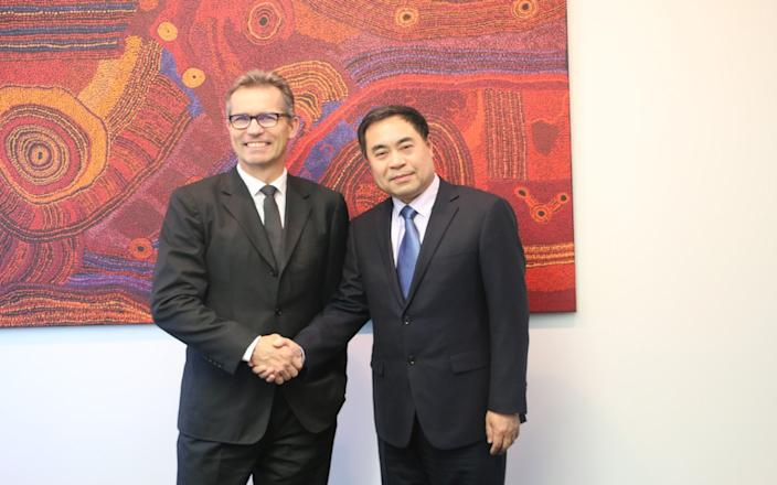 Peter Høj, vice chancellor of the University of Queensland, shakes hands with Chinese consul general Xu Jie.