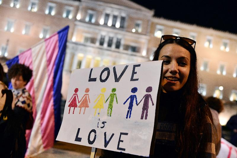 """A woman holds a sign reading """"Love is love"""" during a demonstration outside the Greek parliament in Athens on December 22, 2015 (AFP Photo/Louisa Gouliamaki)"""
