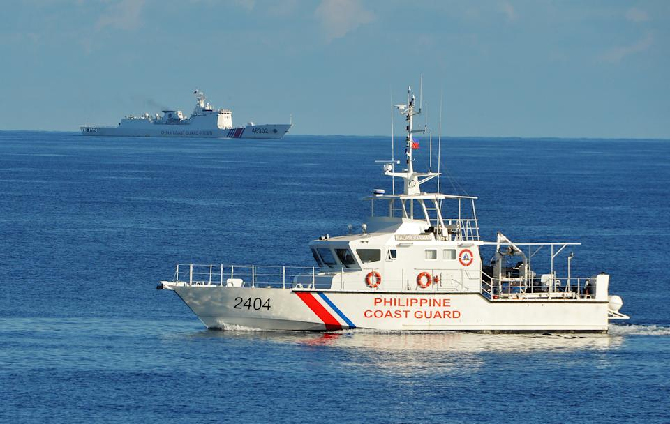 FILE PHOTO: This photo taken on May 14, 2019, a Philippine coast guard ship (R) sails past a Chinese coastguard ship during an joint search and rescue exercise between Philippine and US coastguards near Scarborough shoal, in the South China Sea. (Photo:TED ALJIBE/AFP/Getty Images)