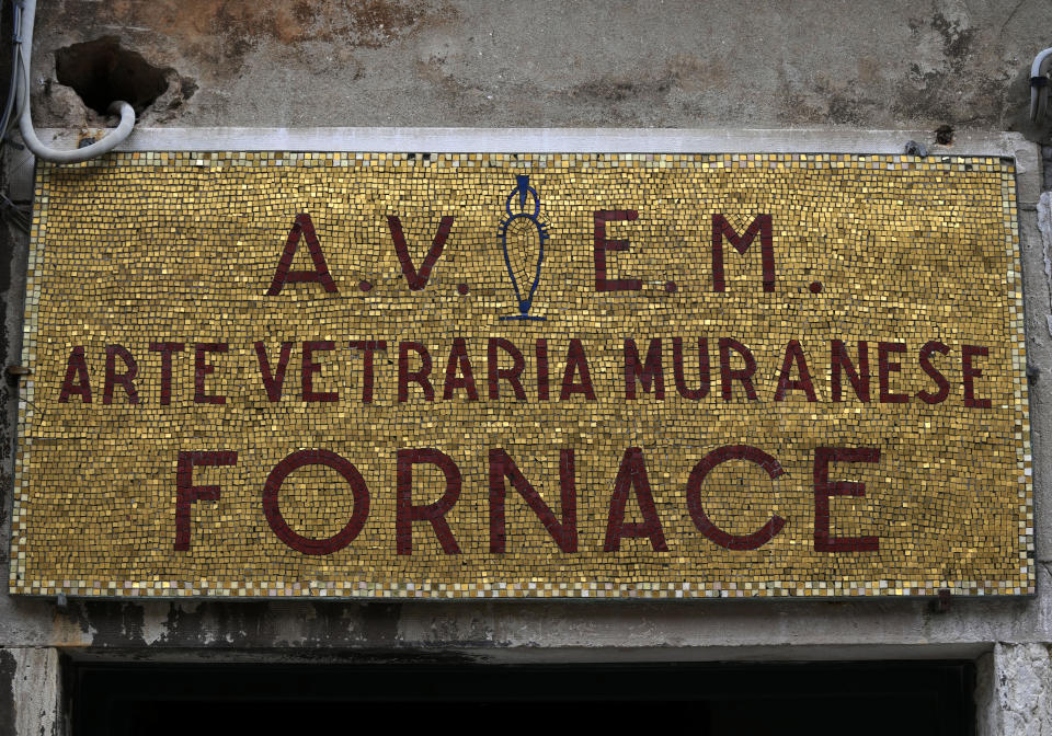 A mosaic with the name of a historical Murano artistic glass furnace is seen in Murano island, Venice, Italy, Thursday, Oct. 7, 2021. The glassblowers of Murano have survived plagues and pandemics and have transitioned to highly prized artistic creations to outrun competition from Asia, but surging energy prices may be their doom. (AP Photo/Antonio Calanni)