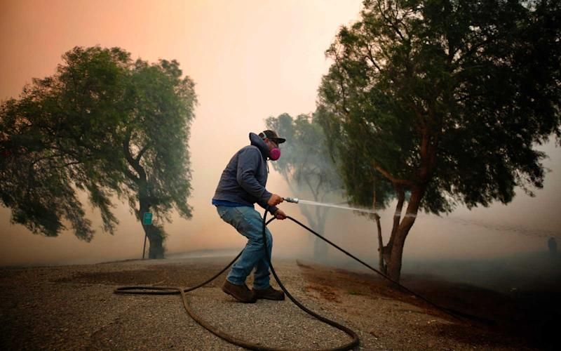 Billy Macfarlane uses garden hose to put out embers threatening his family's ranch on Tierra Rejada Road as the Easy fire approaches October 30, 2019 in Simi Valley, California. | Al Seib/Getty Images
