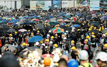 Protesters carry umbrellas as they attends a demonstration in support of the city-wide strike and to call for democratic reforms in Hong Kong