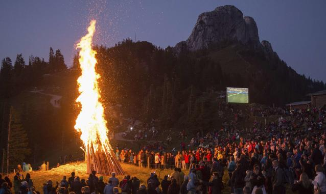 People gather around a bonfire and watch the 2014 World Cup Group G soccer match between Germany and Ghana on an outdoor film projector, during the Sonnwendfeuer (Midsummer) Festival at Mt. Kampenwand in Bavarian Alps, Aschau, 100 km (62 miles) south of Munich, June 21, 2014. Picture taken June 21, 2014. REUTERS/Lukas Barth (GERMANY - Tags: TPX IMAGES OF THE DAY SPORT SOCCER WORLD CUP SOCIETY ENVIRONMENT)