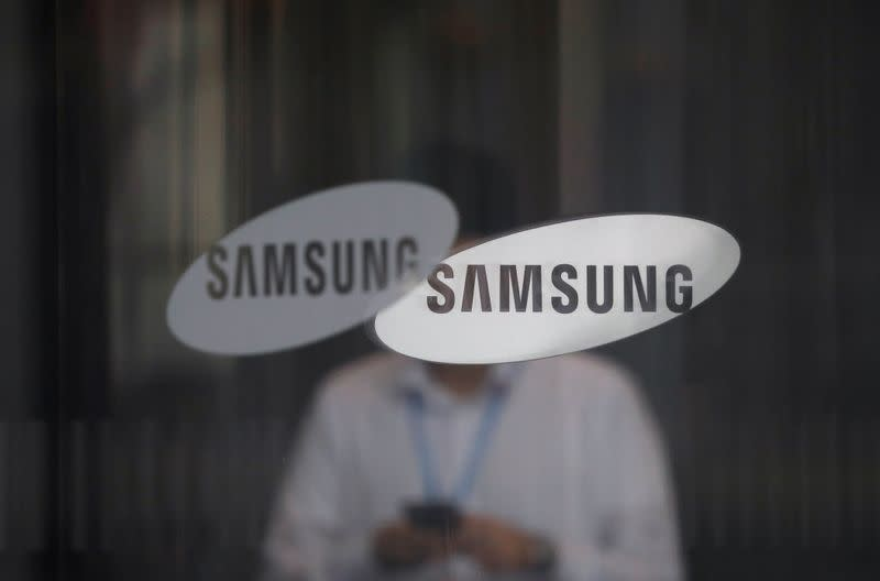 An employee using his mobile phone walks past the logo of Samsung Electronics at its office building in Seoul
