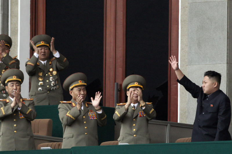 FILE - In this Saturday April 14, 2012 file photo, North Korean leader Kim Jong Un, left, waves as North Korean military officers clap at a stadium in Pyongyang during a mass meeting called by the Central Committee of North Korea's ruling party. Kang Dong-wan, a cross-border relations expert at Dong-A University in Busan, believes South Koreans should start taking North Korean threats more seriously than before because Pyongyang's young leader, Kim Jong Un, is still tightening his grip on power and has not been proven to make sound military judgments. (AP Photo/Ng Han Guan, File)