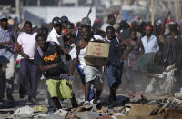 <p>A man runs with a box during sporadic looting in the aftermath of the Jan. 12 earthquake in Port-au-Prince, Thursday, Jan. 28, 2010. (Photo: Ariana Cubillos/AP) </p>